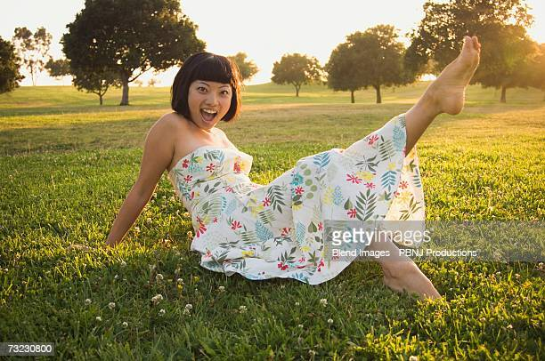 Young Asian woman kicking up foot in grass outdoors