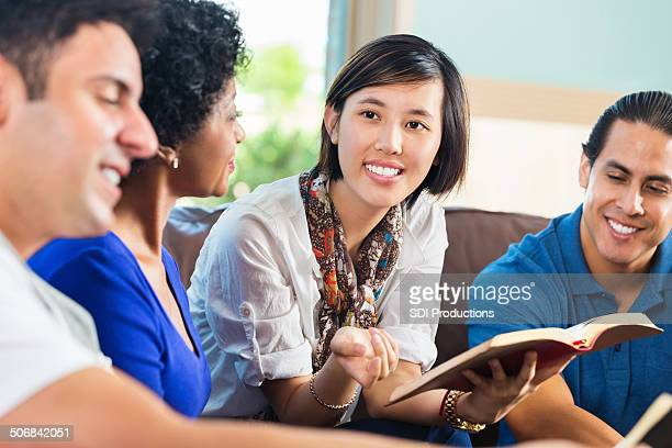 Young Asian woman leading Bible study group at home