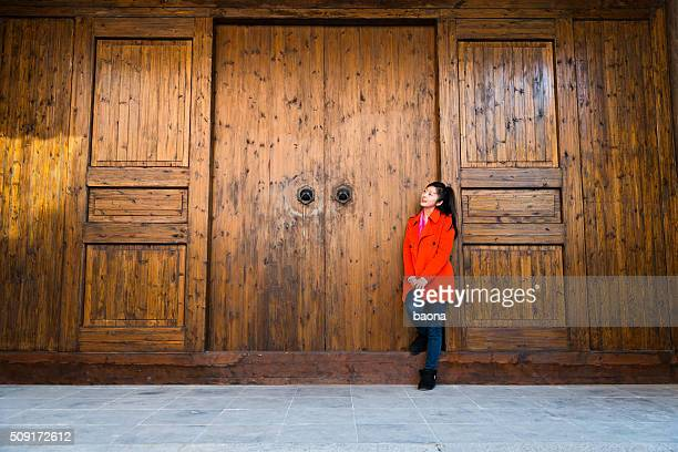 Young asian woman leaning in wood door