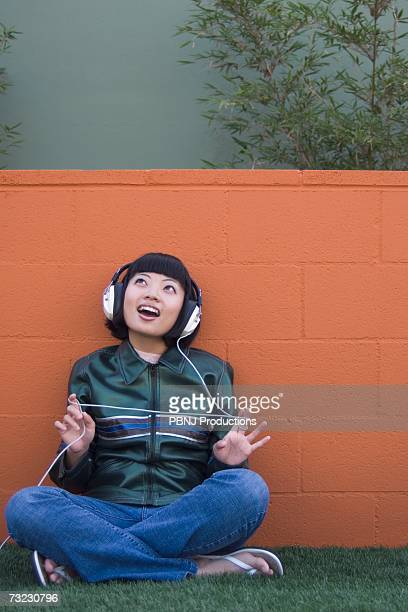 Young Asian woman listening to headphones outdoors