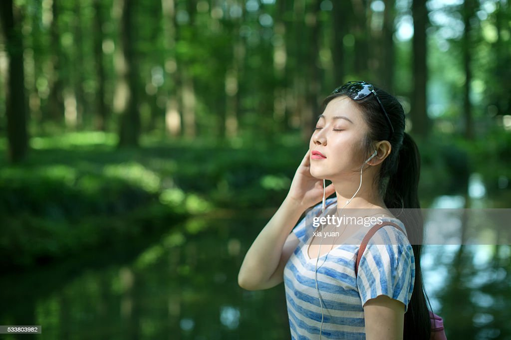Young asian woman listening to music in forest,with eyes closed : Foto stock