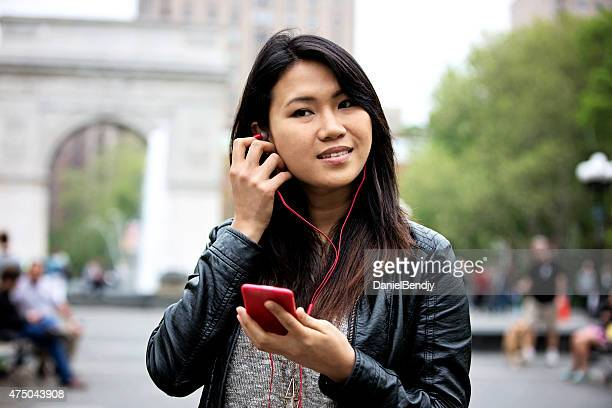 young asian woman listening to music on her mobile phone - washington square park stock pictures, royalty-free photos & images