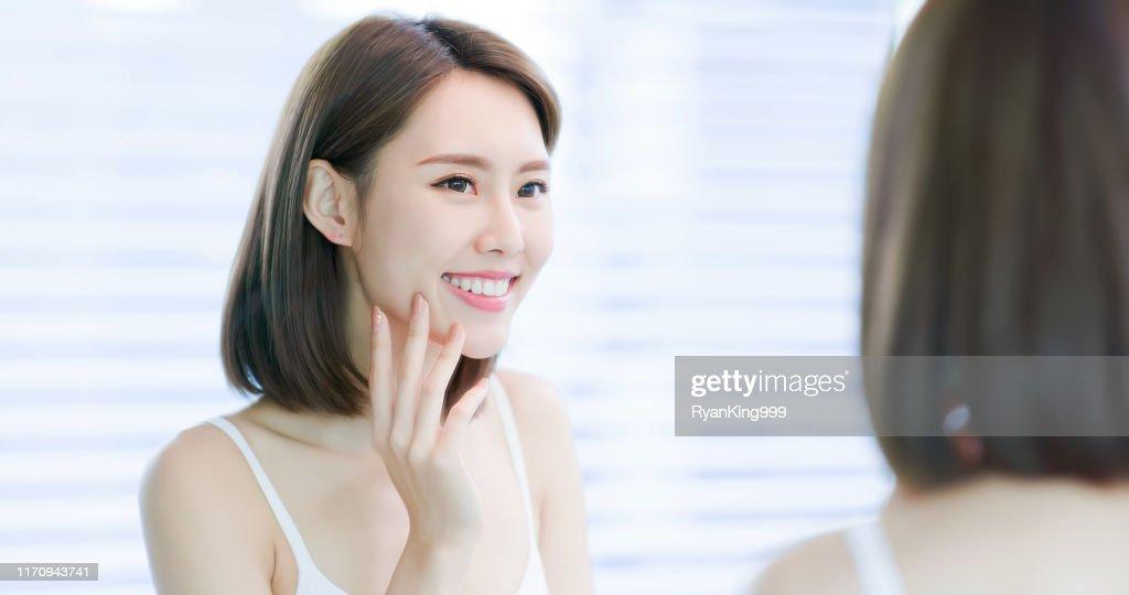 若いアジアの女性は鏡を見る : ストックフォト