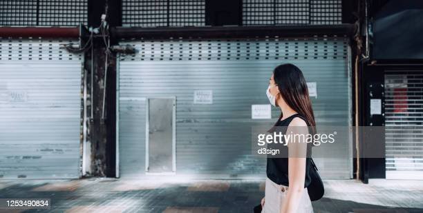 young asian woman looking at closed shops while walking on city street. economic depression due to covid-19 outbreak - closed stock pictures, royalty-free photos & images
