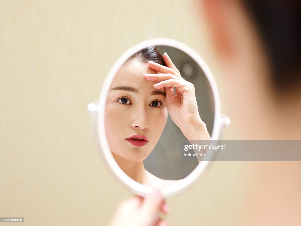 young asian woman looking at self in mirror : Stock Photo
