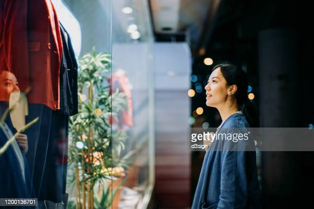 young asian woman looking at shop window while walking in the city at night - merchandise stock pictures, royalty-free photos & images