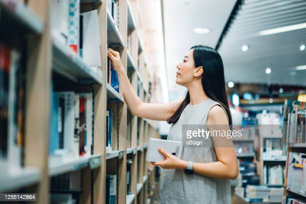 young asian woman looking for books from bookshelf in book store - literature stock pictures, royalty-free photos & images