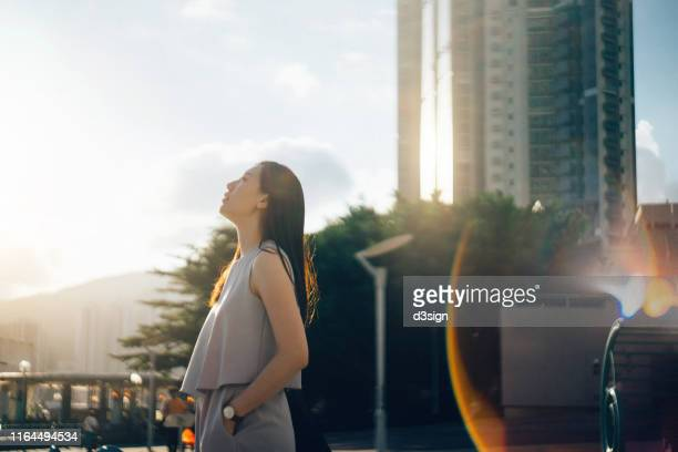 young asian woman looking up to sky in deep thought in the city at sunset - lichtvlek stockfoto's en -beelden