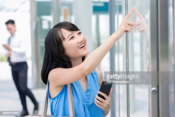 Young Asian woman looks at map at train station