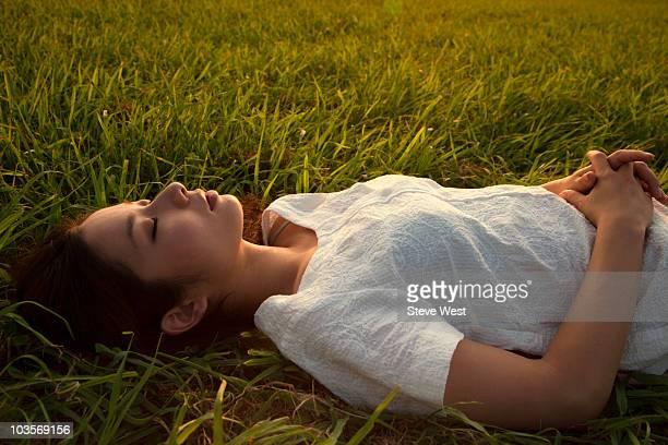 young asian woman lying in grass at sunset - handen op de buik stockfoto's en -beelden