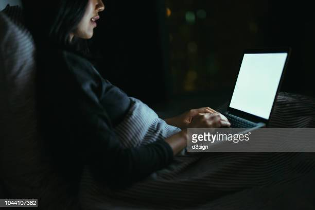 young asian woman lying on bed using laptop at night - search engine stock pictures, royalty-free photos & images