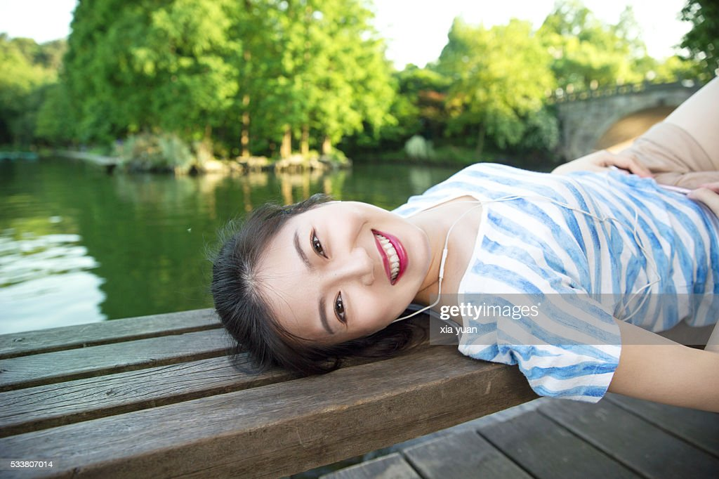 Young asian woman lying on pier above lake,listening to music : Foto stock