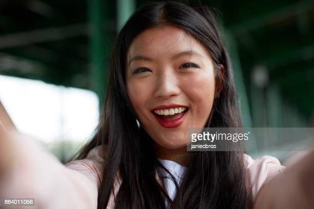 Junge Asiatin macht Selfie unter der Brücke. Fröhlich