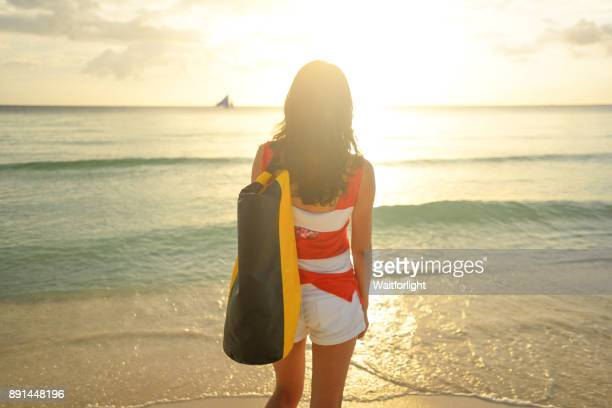 Young asian woman on beach at sunset