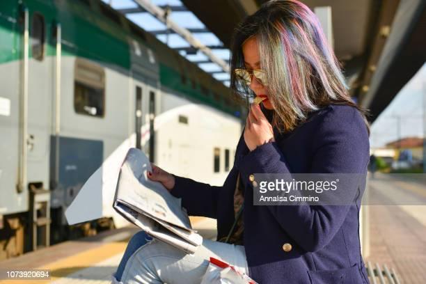 young asian woman on train platform - bahnreisender stock-fotos und bilder