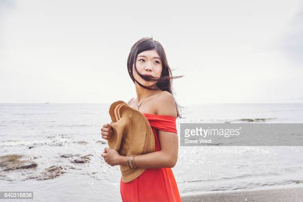 Young Asian Woman On Windy Beach Holding Hat