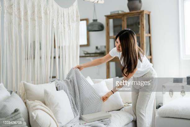 junge asiatische frau organisieren und aufräumen die kissen und werfen auf dem sofa im wohnzimmer zu hause - designer einrichtung stock-fotos und bilder