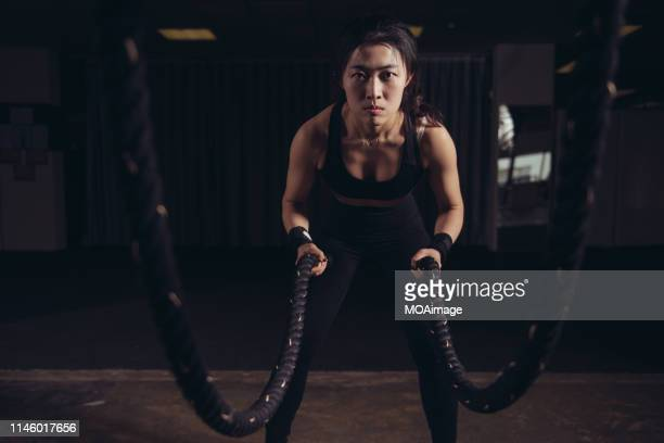a young asian woman performs strength training in a gym - concentration stock pictures, royalty-free photos & images