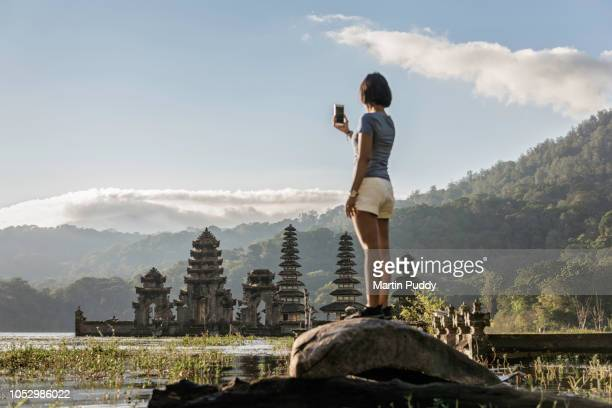 young Asian woman, photographing Tamblingan temple, using smart phone