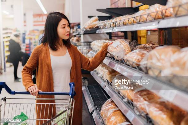 young asian woman picking up bread in grocery store with a trolley - east asian ethnicity stock pictures, royalty-free photos & images