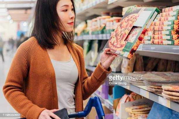 young asian woman picking up pizza in grocery store - ready to eat stock pictures, royalty-free photos & images