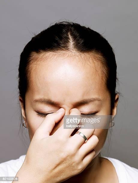 young asian woman pinching bridge of nose