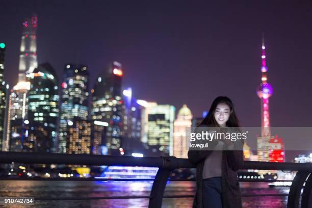 junge asiatische Frau spielt mit Handy in modernen Stadt