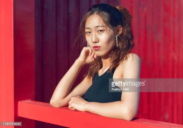young asian woman posing against a red background outdoors - armpit hair woman stock pictures, royalty-free photos & images