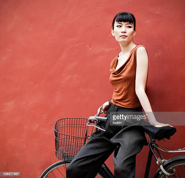 young asian woman posing sitting on bicycle - korean ethnicity stock pictures, royalty-free photos & images