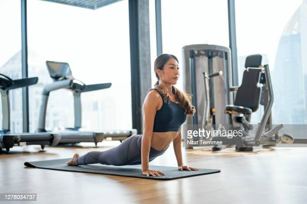 young asian woman practicing a cobra pose during her yoga routine at health club center. self improvement, active lifestyle. - center athlete stock pictures, royalty-free photos & images