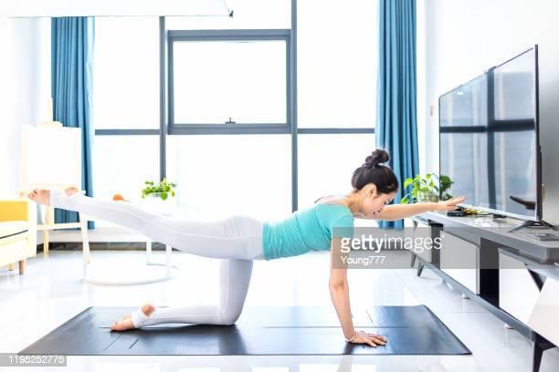 リビングルームでヨガを練習している若いアジアの女性 - 練習 ストックフォトと画像