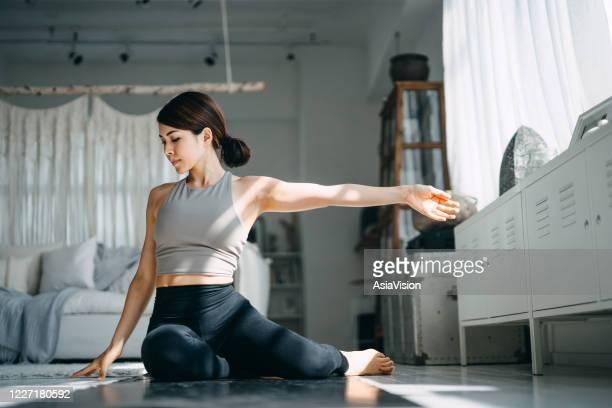 junge asiatische frau, die morgens yoga im wohnzimmer zu hause praktiziert - turner syndrome stock-fotos und bilder
