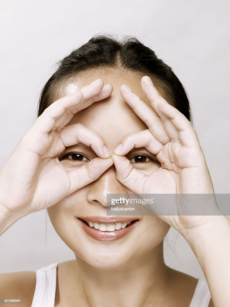 Young asian woman pretending fingers are glasses : Stock Photo