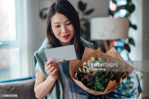 young asian woman reading greeting card attached and holding flower bouquet - remote location stock pictures, royalty-free photos & images