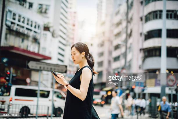 Young Asian woman reading text messages on smartphone while walking in busy downtown city street