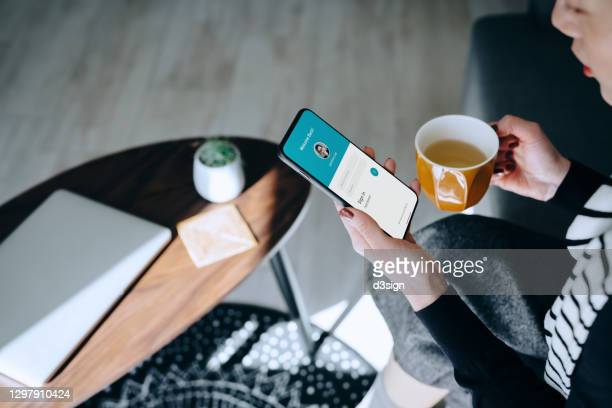young asian woman relaxing at home drinking a cup of tea, logging in to her smartphone device. lifestyle business, privacy protection, internet and mobile security concept - verification stock pictures, royalty-free photos & images