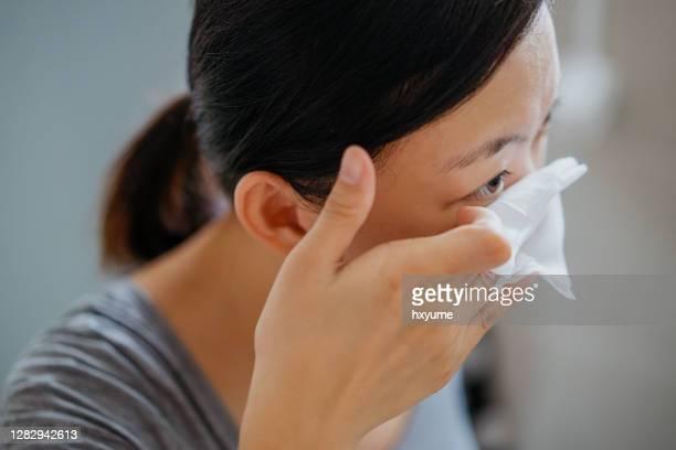 メイクアップリムーバーワイプでメイクアップを削除する若いアジアの女性 - アイメイク ストックフォトと画像
