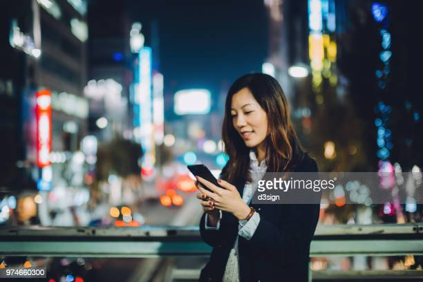 young asian woman requesting a ride with smartphone in downtown city street at night - japan economy stock pictures, royalty-free photos & images