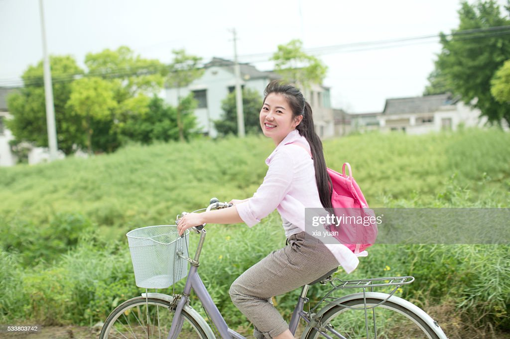 Young asian woman riding bicycle through country rapeseed field : Foto stock