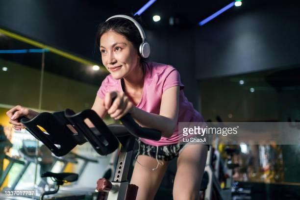 young asian woman riding stationary bike during indoor cycling class in gym. - peloton stock pictures, royalty-free photos & images