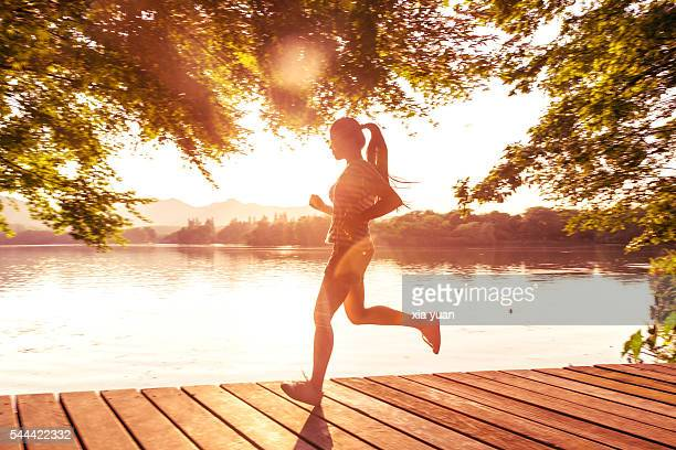 Young asian woman running on pier against lake at sunset