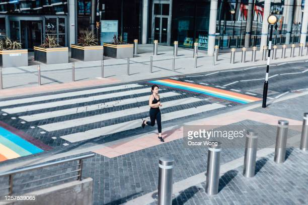 young asian woman running on zebra crossing - animated zebra stock pictures, royalty-free photos & images