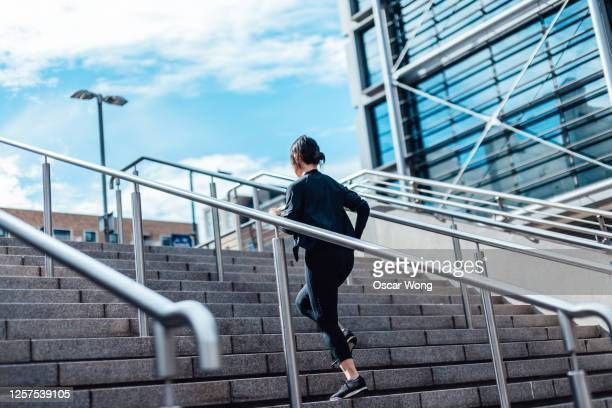 young asian woman running upstairs in finance district - women photos stock pictures, royalty-free photos & images