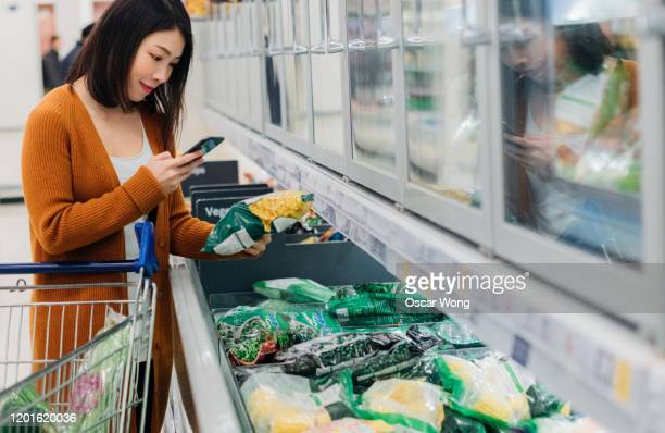 young asian woman scanning barcode on packaging with smart phone in grocery store - frozen food stock pictures, royalty-free photos & images