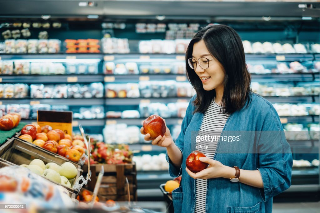 Young Asian woman shopping for fresh organic fruits in supermarket : Stock Photo