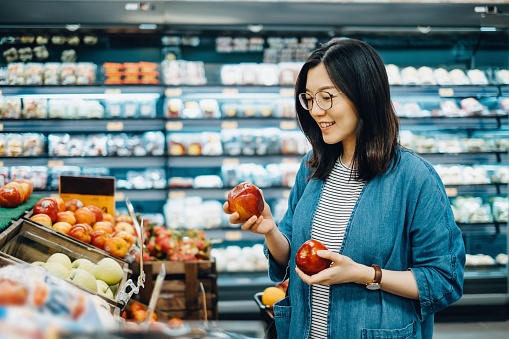 Young Asian woman shopping for fresh organic fruits in supermarket - gettyimageskorea