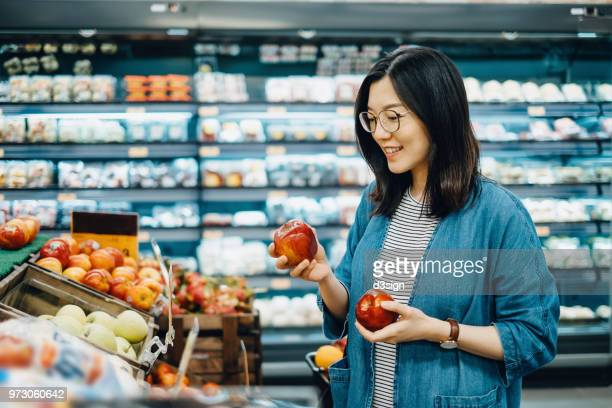 young asian woman shopping for fresh organic fruits in supermarket - consumentisme stockfoto's en -beelden
