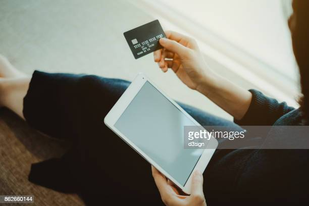 Young Asian woman shopping online with credit card and digital tablet