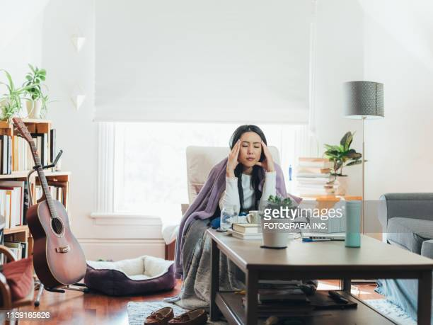 young asian woman sick at home - electric blanket stock photos and pictures
