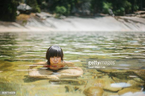A young asian woman sits in crystal clear water